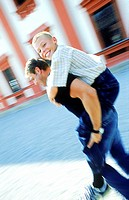 Blurred side profile of a man carrying a boy on his back