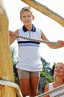 Child holding on a jungle gym with mother standing behind