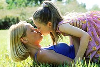 Close-up of mother and daughter lying on a lawn and kissing
