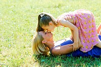 Close-up of mother holding daughter kissing and lying on grass