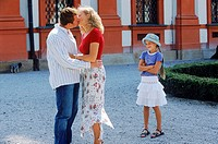 Young couple kissing with daughter standing by smiling