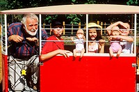 Elderly man with three children in a toy train