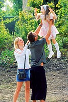 Father mother holding child in air