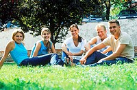A group of young people sitting together on a lawn