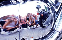 Reflection of a group of friends on a chrome surface