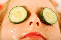Close-up of a woman's eyes covered with cucumber slices