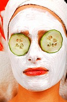 Young woman with a face pack and cucumber slices on eyes