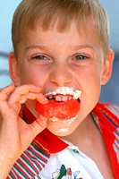 Portrait of a young boy eating sweet
