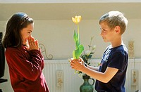 Side profile of a young boy offering a flower to a young girl