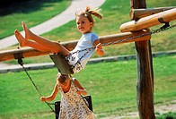 Two young girls playing on swings in the park