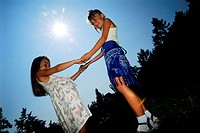 Low angle view of two young girls standing holding hands