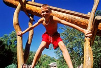 Low angle view of a young boy leaning forward on a jungle gym