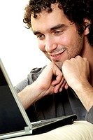 Close-up of a young man in front of a laptop