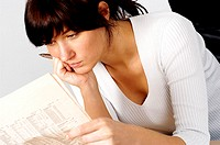 Close-up of a businesswoman reading a financial page