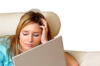 Close-up of a businesswoman lying on a couch in front of a laptop