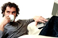 Young man drinking a cup of tea using a laptop