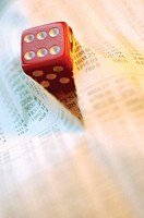 Close-up of a dice on a torn financial page