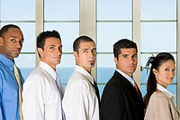 Side profile of four businessmen standing with a businesswoman