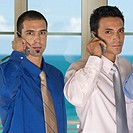 Portrait of two businessmen using mobile phones