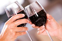Close-up of a man and a woman toasting glasses of red wine