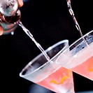 Close-up of a person´s hand pouring martini into martini glasses