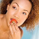 Close-up of a young woman eating a strawberry