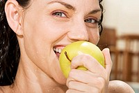 Portrait of a young woman eating a green apple