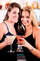 Portrait of two young women toasting martinis in a bar
