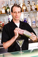 Portrait of a bartender preparing a martini