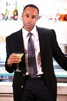 Portrait of a businessman leaning against a bar counter holding a martini glass