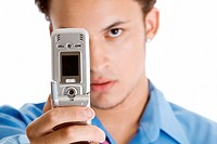 Close-up of a young man taking a photograph of himself with a mobile phone