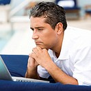 Close-up of a mid adult man lying down in front of a laptop