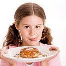 Portrait of a girl holding a donut in a plate licking her lips (thumbnail)