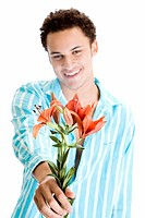 Young man holding flowers and smiling