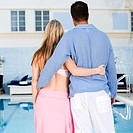 Rear view of a young woman and a mid adult man standing at the poolside