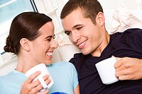 Close-up of a young couple holding coffee cups looking at each other