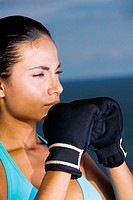 Close-up of a young woman wearing boxing gloves (thumbnail)