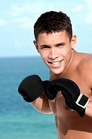 Portrait of a young man wearing boxing gloves (thumbnail)