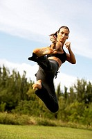 Low angle view of a mid adult woman practicing martial arts (thumbnail)