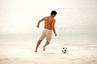 Rear view of a mid adult man playing soccer on the beach