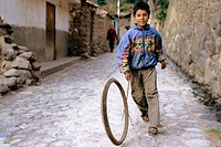 Peruvian boy playing on a narrow cobblestone street from the inca period. Ollantaytambo, Perù