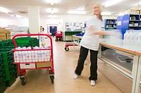 Hospital pharmacy. Pharmacy technician loading a trolley with medical supplies.