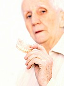 False teeth. Elderly woman holding a pair of false teeth in her hand. These are designed to fit an individual´s mouth, and replace teeth lost through ...