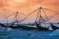 Boats with traditional Chinese fishing nets on beach, Cochin, Kerala, India