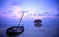 Silhouette of hut and boat in sea, Maldives