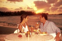 Young couple having dinner on the beach