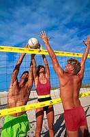 Two men and woman playing volley ball on beach