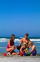 Couple playing with their two children on beach