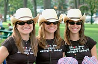 Three sisters triplets with cowboy hats and smiles