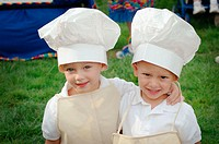 Twin kids children looking alike and like cooks with tall hats
